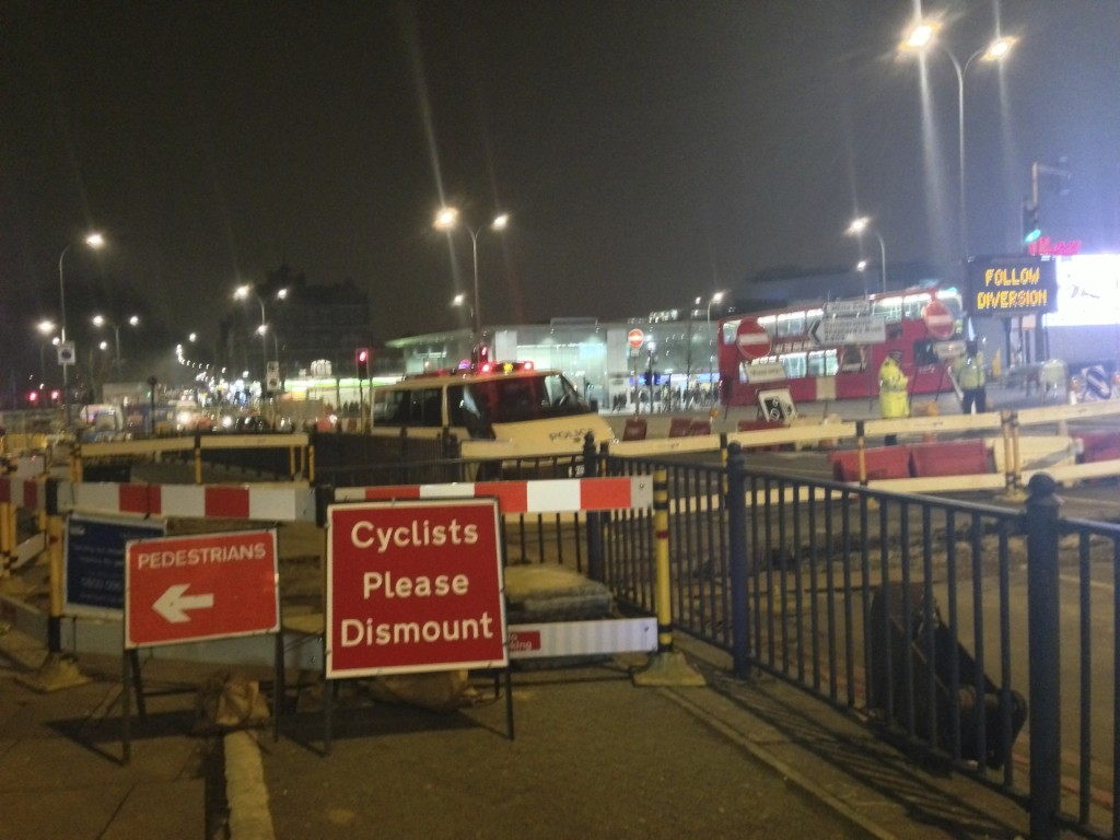 A great example of it going wrong - cylists directed first to dismount then into a narrow space with pedestrians at Holland Park Roundabout, February 2013
